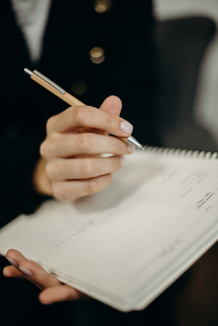 person holding orange click pen writing on notebook